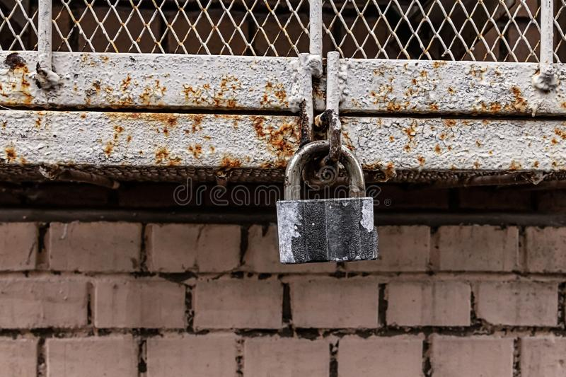 Old weathered closed gray padlock against the background of an iron box grating walls industrial background stock images