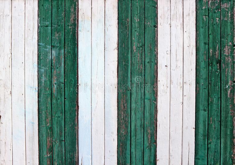 Old weathered colored wooden wall made of vertical stripes, with green and white peeled paint. Background for copy text stock image