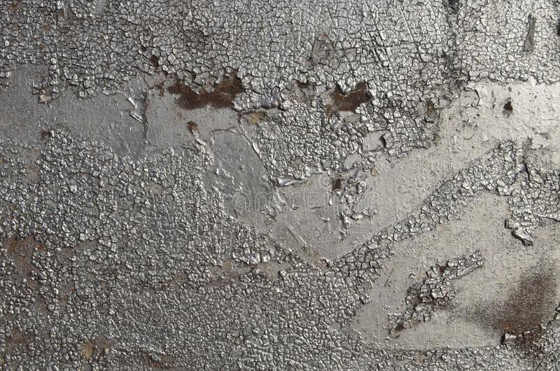 Old weathered cracked peeling airbrushed silver graffiti paint. Metal surface sprayed with graffiti paint of silver color. Rough texture of the old weathered stock photography