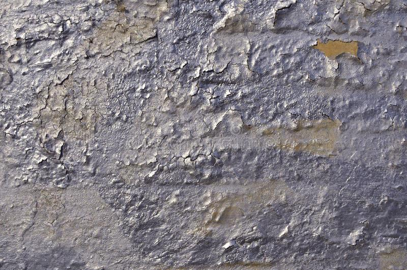 Old weathered cracked peeling glossy airbrushed graffiti paint. Of silver, purple colors on concrete wall. Background royalty free stock photo