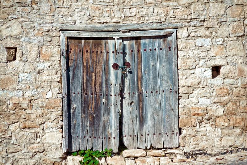 Old weathered door in a stone wall. Cyprus stock photography
