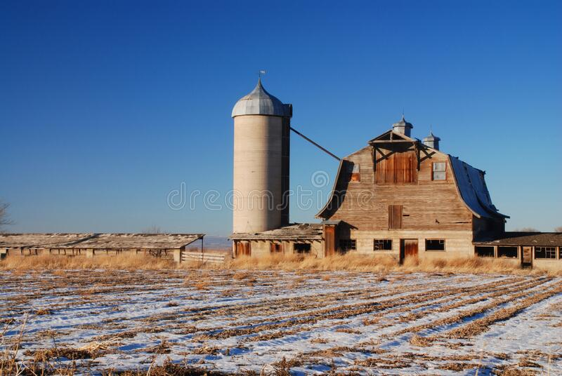 Old barn near a silo under the blue sky royalty free stock photography