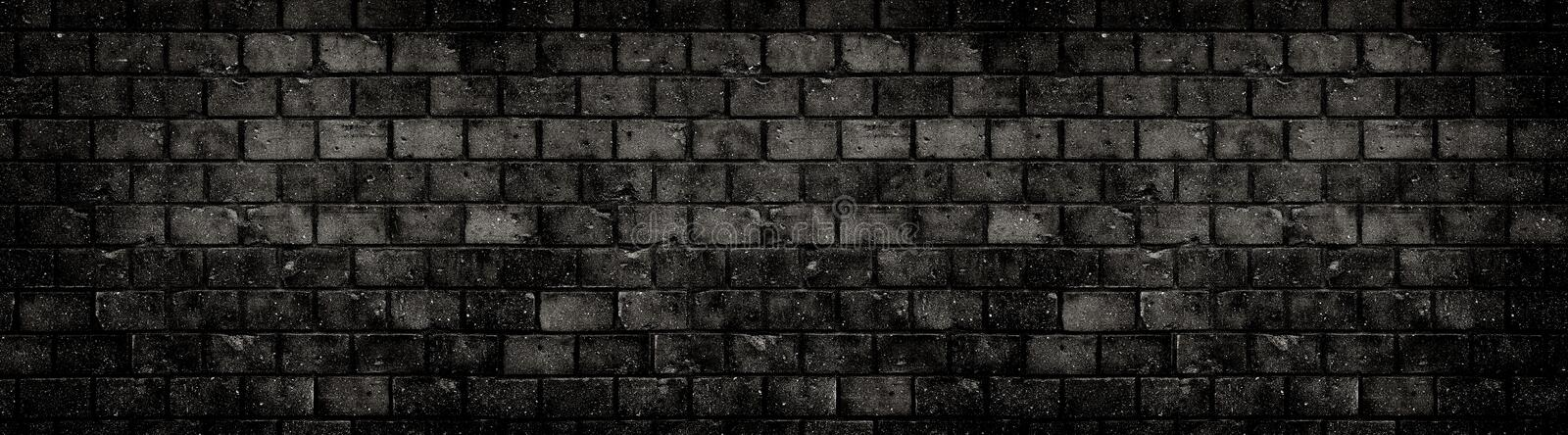 Old weathered grungy black dark concrete block brick wall texture background abandoned house holes cracks wide banner background royalty free stock photography