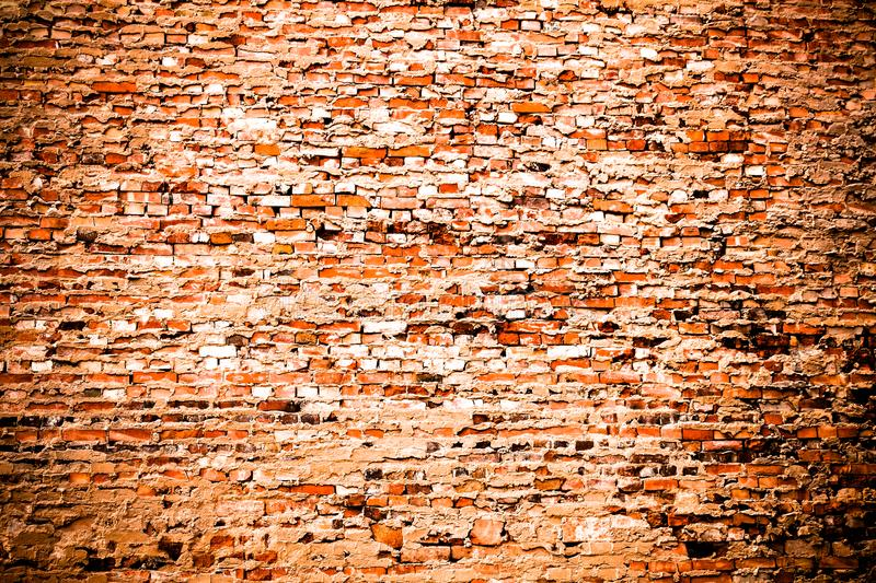 Red brick wall background:old weathered grungy red orange brick wall covered by cement and grey paint texture background royalty free stock photography