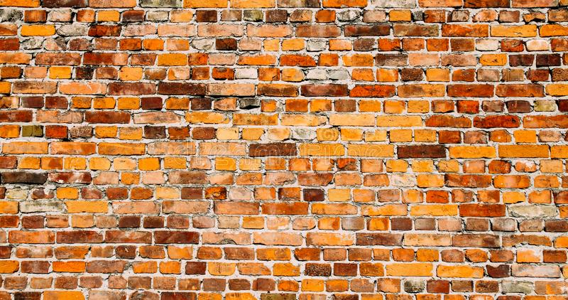 Old and weathered grungy yellow and red brick wall as seamless pattern texture surface background in wide banner format.  stock photos