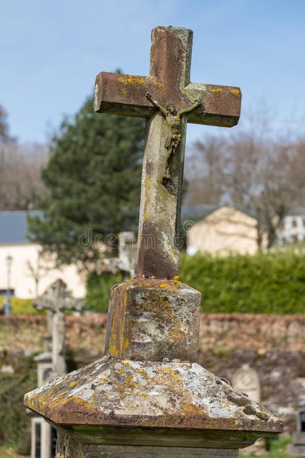 Old Weathered Leaning Stone Crucifix. On cemetary in Girsterklaus, Luxxembourg royalty free stock photography