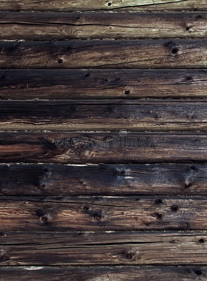 Old weathered log wall. Dark brown wooden background. Craked shabby logs royalty free stock photography