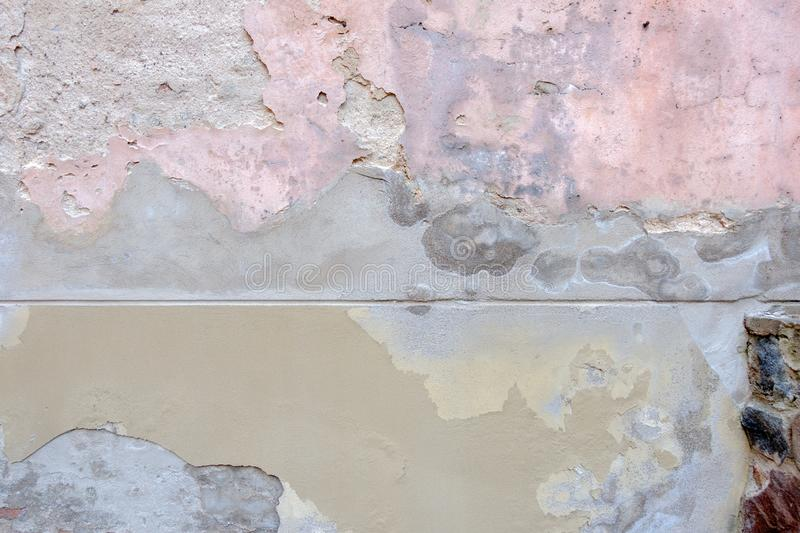 Old weathered painted wall background texture.Beige grey pink dirty peeled plaster wall with falling off flakes of paint stock photography