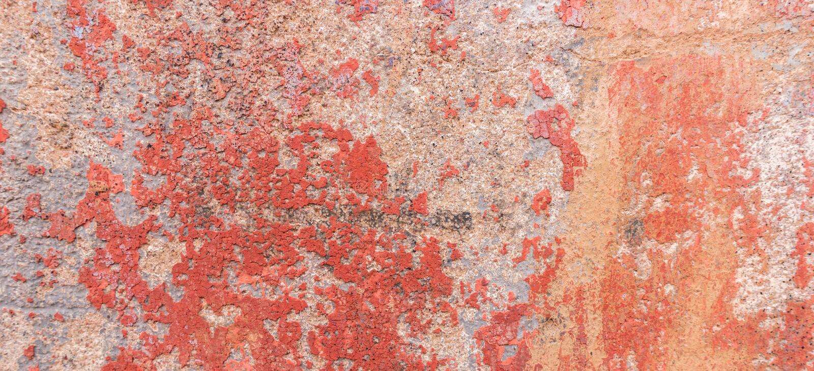 Old weathered painted wall background texture. Red dirty peeled plaster wall with falling off flakes of paint. stock image