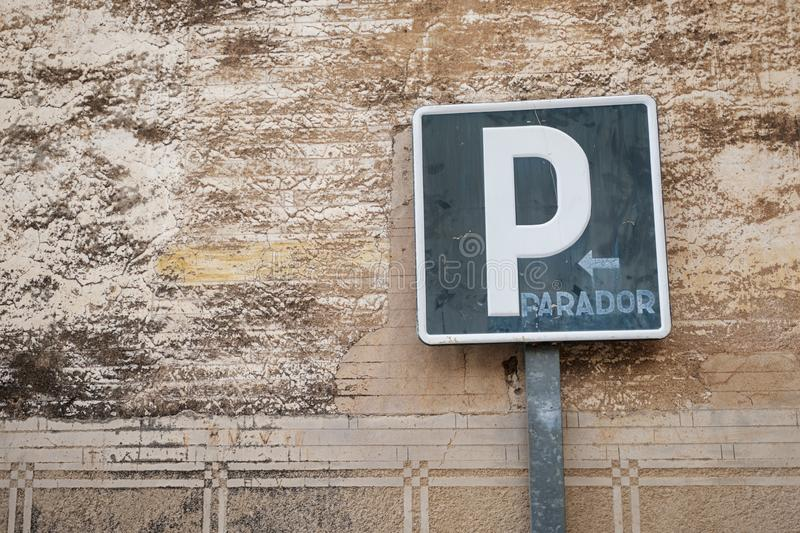 Old weathered parking traffic sign against a stucco old wall royalty free stock photo