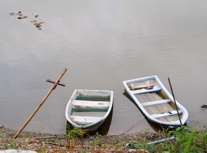 Old weathered plastic fade out color boats on smooth water surface. Old weathered plastic fade out color boats on a small smooth water surface grey brown lake royalty free stock photos
