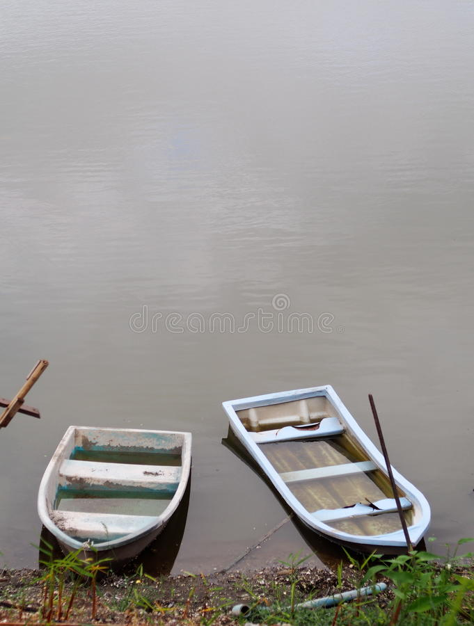 Old weathered plastic fade out color boats on smooth water surface royalty free stock photography