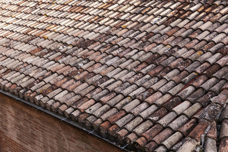Old weathered red tile roof close-up photo. Background texture stock photography