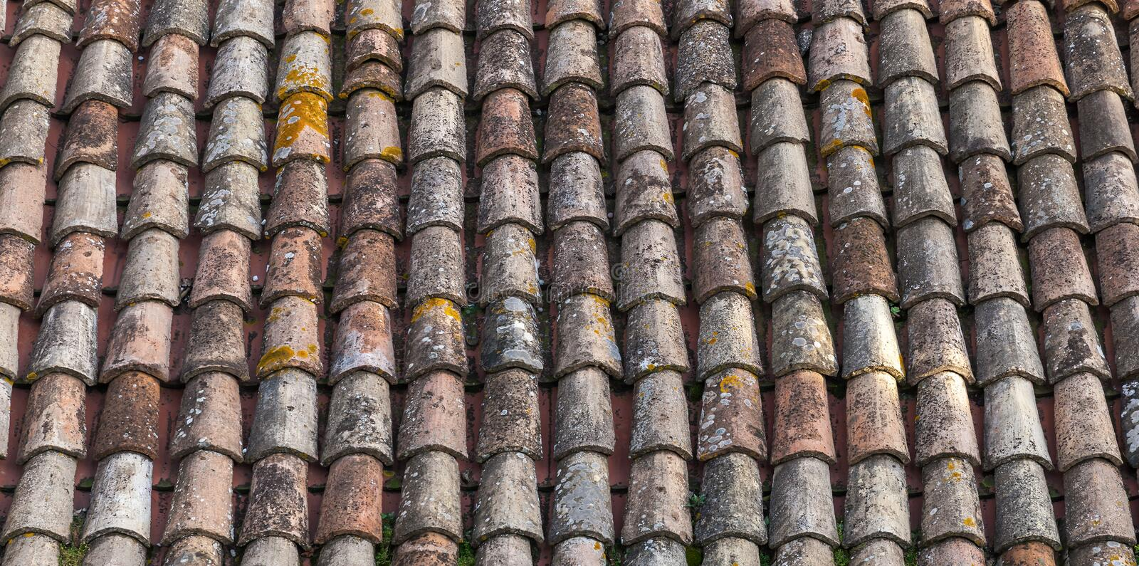 Old weathered red tile roof closeup photo. Background. Texture stock images