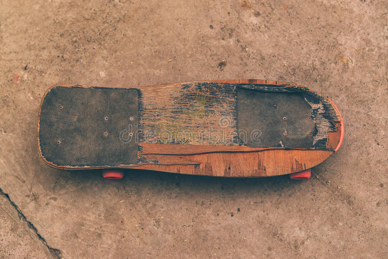 Old weathered skateboard on concrete surface stock photo