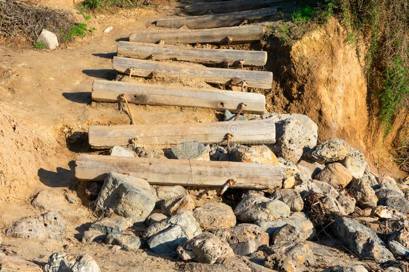 Old weathered stairs made from wooden logs leading to the beach. Ending on rocks royalty free stock images