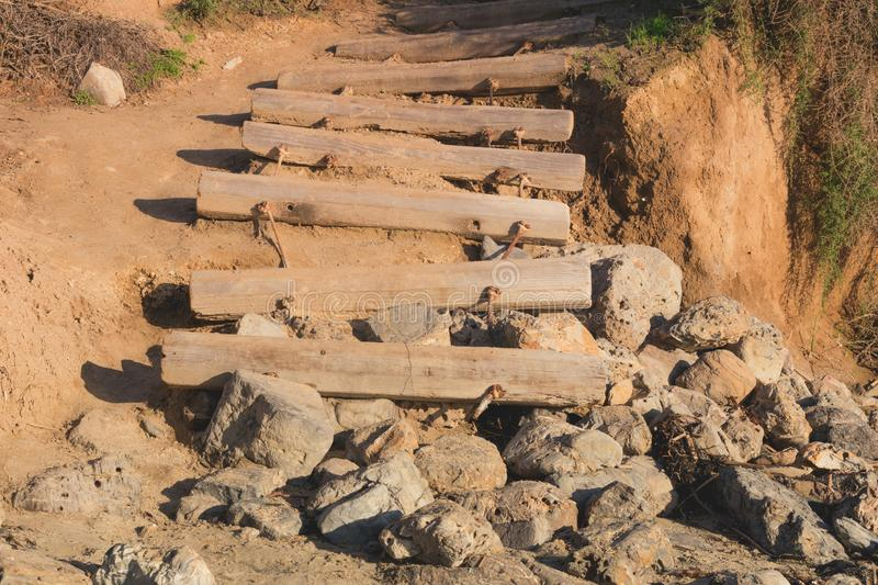 Old weathered stairs made from wooden logs leading to the beach. Ending on rocks royalty free stock photography