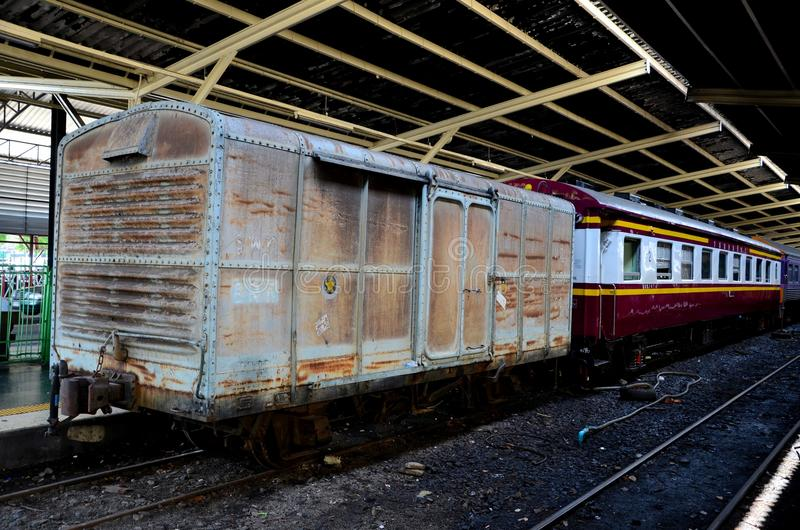 Old weathered Thai rail boxcar parked at station platform Hua Lamphong Bangkok Thailand. Bangkok, Thailand - May 4, 2017: An old brown painted weathered boxcar royalty free stock photo