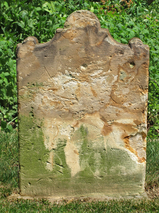 Old weathered tombstone . Old, weathered, and worn nameless stone slab grave tombstone royalty free stock photo