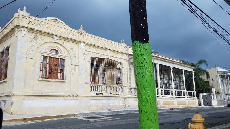 Old weathered white building in Puerto Rico with utility pole with green paint. Old weathered or worn white building in Puerto Rico with wood utility pole with stock photo