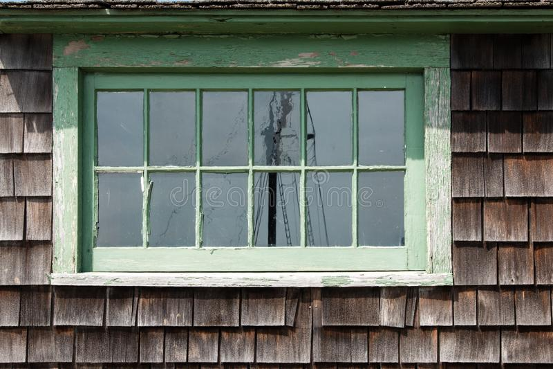 Old weathered window with a reflection. An old cedar shingled house has a window with green, chipped paint trim. The window reveals a reflection of a sailboat royalty free stock photo