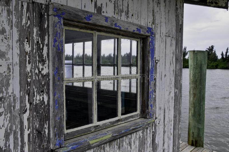Old weathered window on a shack on a florida waterway. Closeup view royalty free stock image