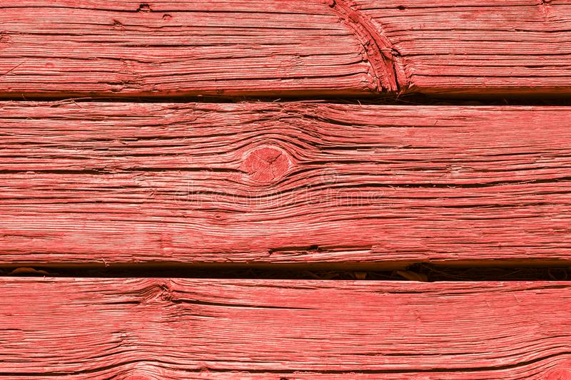 Old weathered wooden plank painted in living coral stock photo