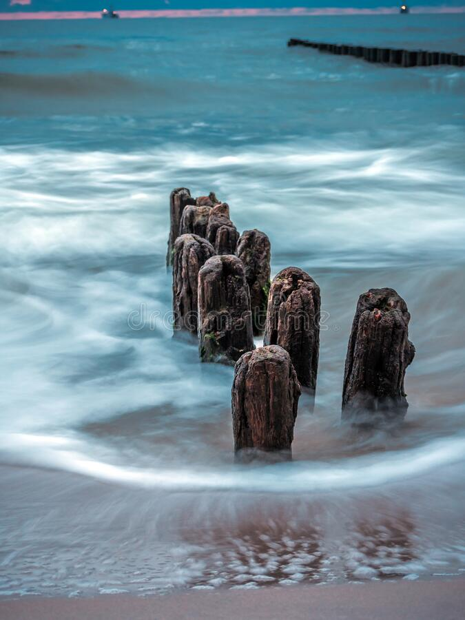 Old and weathered wooden wave breakers stock image