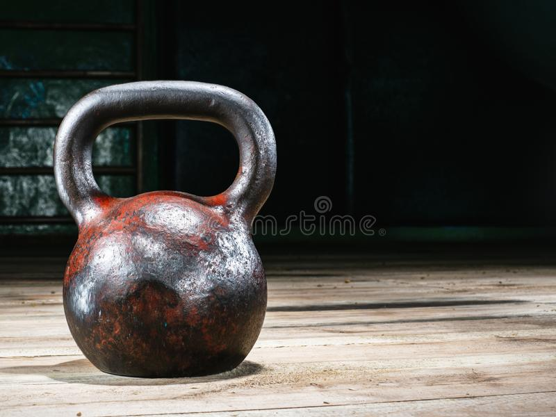Old weight in the gym. Old rusty sport weight in a gym on a wooden floor royalty free stock photography