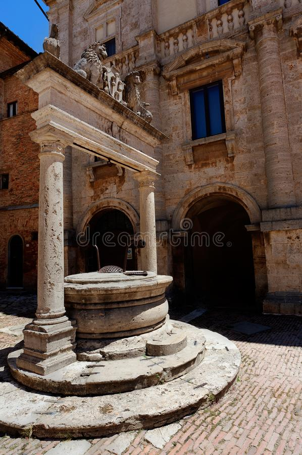 Antique well Piazza Grande square, Montepulciano, Tuscany, Italy. Old well decorated with griffins and lions holding symbol or coat of arms with balls, bolls of stock photography