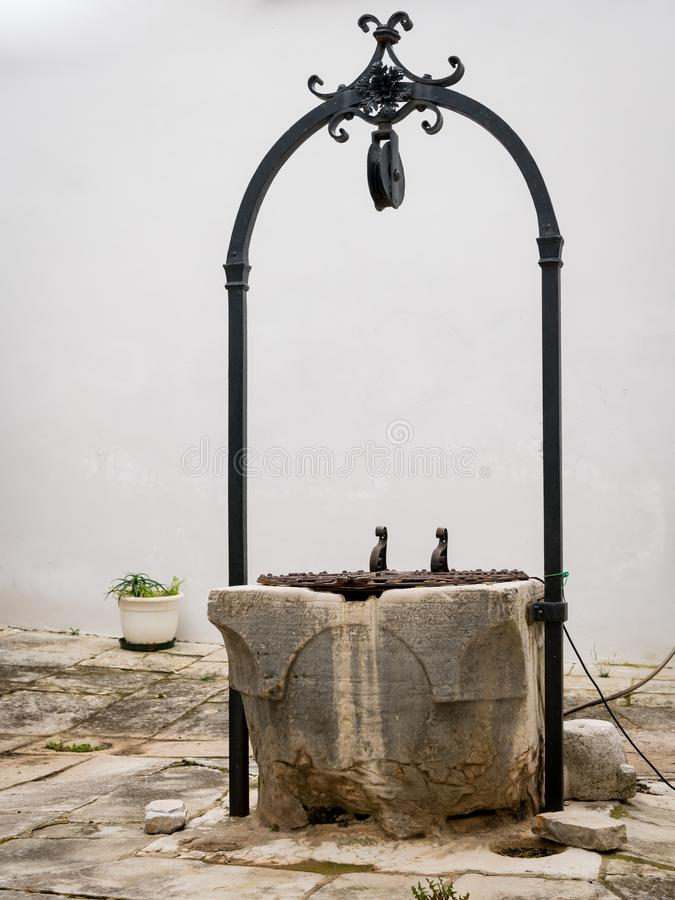 Old well, inner courtyard of church Sveti kriz in Cres stock photography