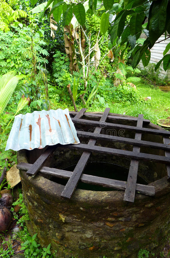Old well with safety grid, farm house