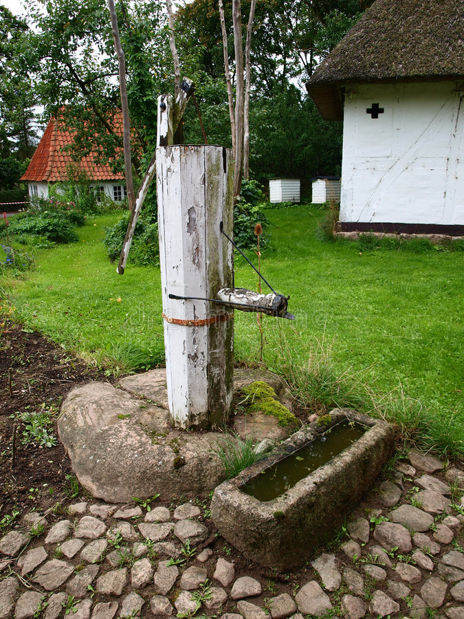 Old well water pump in a farm. Old vintage well water pump in village farm Denmark stock photo