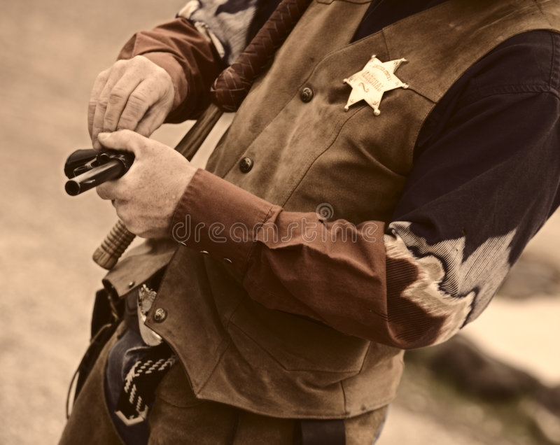 Old West-Lock And Load. The Marshall loads his gun before the shoot out stock photo