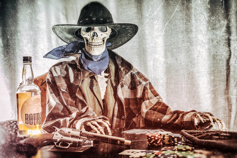 Old West Poker Skeleton Bourbon Gun. Old west bandit outlaw skeleton at a poker table with a pistol and bourbon edited in vintage film style stock photos
