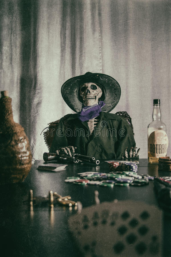 Old West Poker Skeleton Dead Mans Hand. Old west bandit outlaw skeleton at a poker table with a pistol and bourbon, cards showing aces and eights (dead man's royalty free stock photography