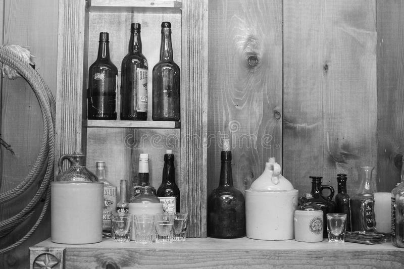Old West Saloon. Black and white photo of an old west saloon with antique bottles and a nice western wood backdrop stock photo