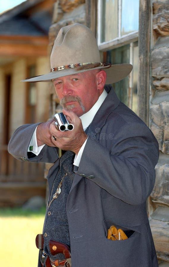 Old West Sheriff. Raises rifle stock photo