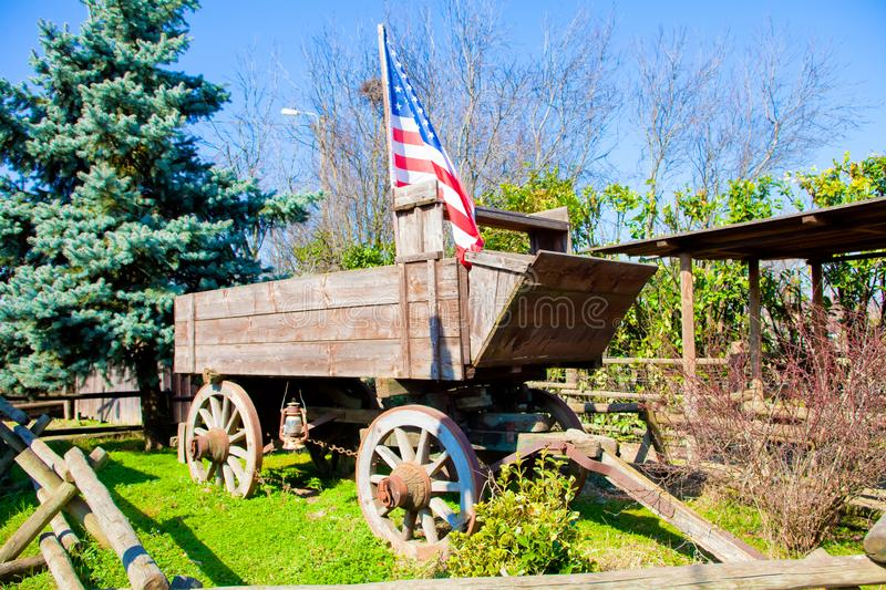 Old west wooden wagon with flag royalty free stock photo