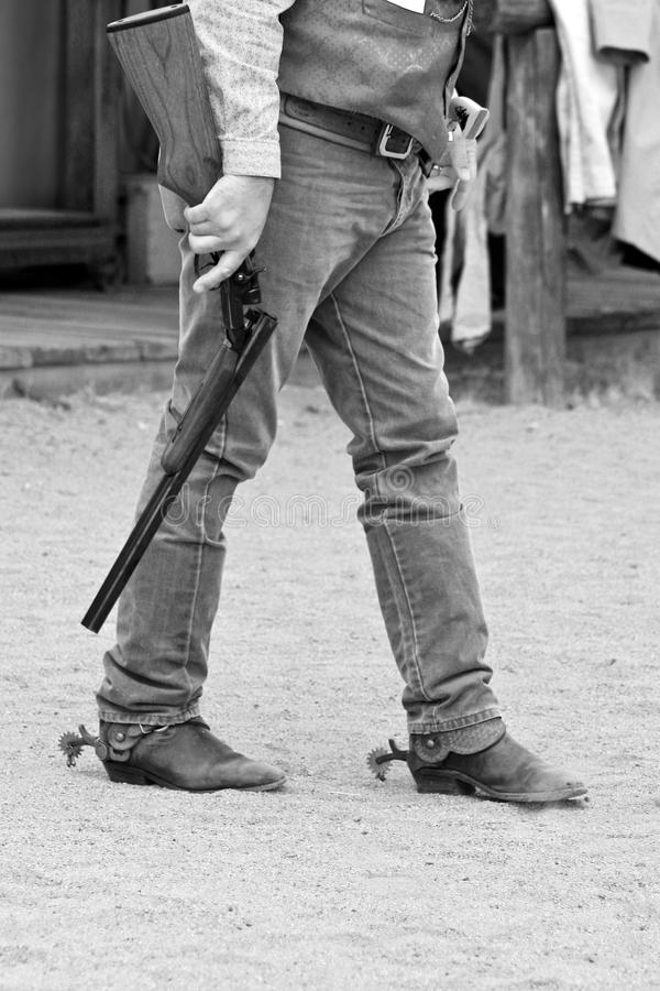 Old Western Sheriff With Shotgun. Old western town sheriff crosses the street with his shotgun at his side royalty free stock photos
