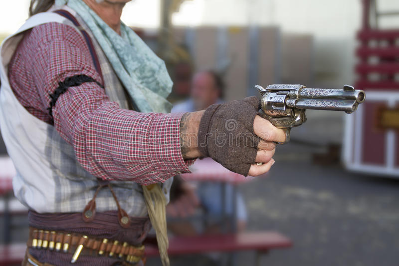 Old Western Outlaw Cowboy Gunfighter. Old western town cowboy gunfighter aims a six gun in Arizona stock photos
