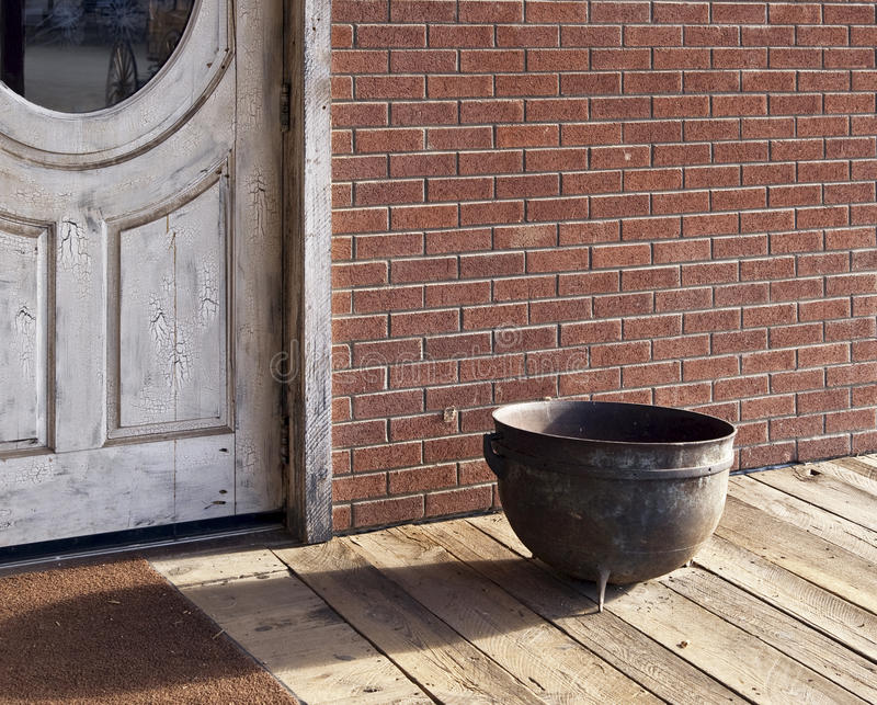 Old Western town saloon door and spittoon. Old Western town saloon door with wood sidewalk and spittoon stock photos