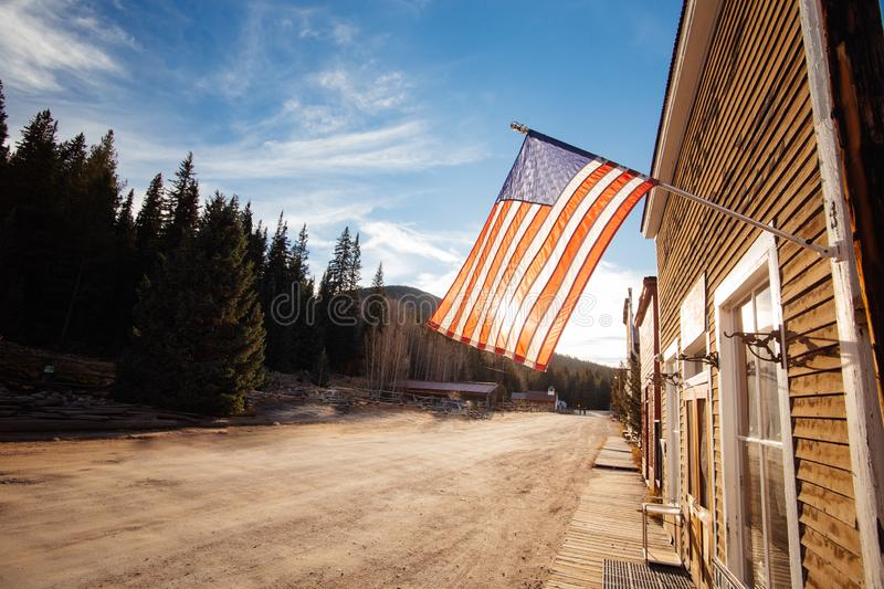 Old Western Wooden Buildings with flag of the united states, in St. Elmo Gold Mine Ghost Town in Colorado. USA hidden in mountains royalty free stock photo