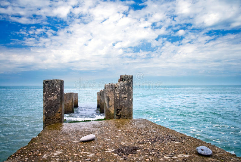 Old wet pier. Black Sea coast: old wet pier with columns with perfect sky and sea on background. Russia, Sochi, Adler stock images