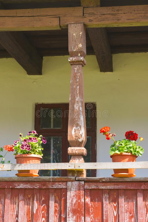 Old wethered wood porch, pole, window, roof structure and geranium flower pots stock images