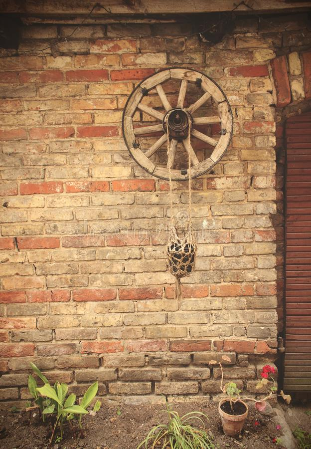 Old wheel and potted plant hanging on old brick wall. Old wheel and potted plant hanging on old yellow and red brick wall, abstract, ancient, architecture stock photo