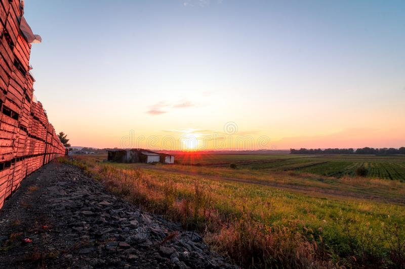 Old white barn lined with onion crates at late summer sunset royalty free stock photo