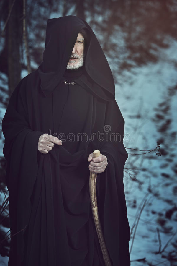 Old white beard pilgrim in dark forest with snow. Fantasy and mythology royalty free stock photos