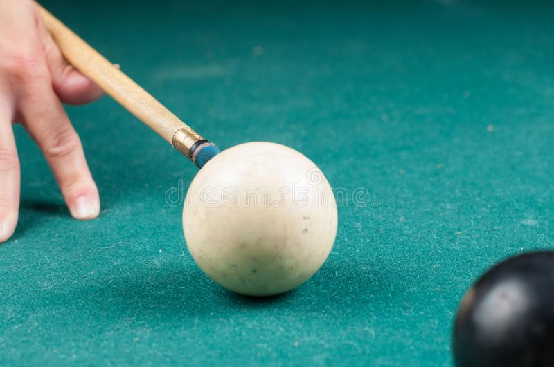 Old white billiard ball and stick on a green table. billiard balls isolated on a green background. Old  white billiard ball  and stick on a green table. billiard royalty free stock photo