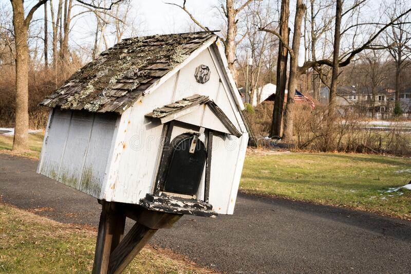 Old white wooden bird box used as mailbox. Winter in Scotch Plains, New Jersey. Birdcages are usually found in some gardens in the area royalty free stock photo